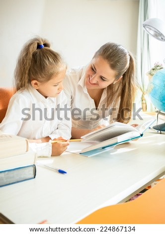 Portrait of cute daughter doing homework with mother - stock photo