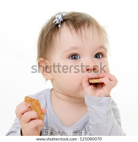 portrait of cute eating little girl toddler, 10 month, studio over white - stock photo
