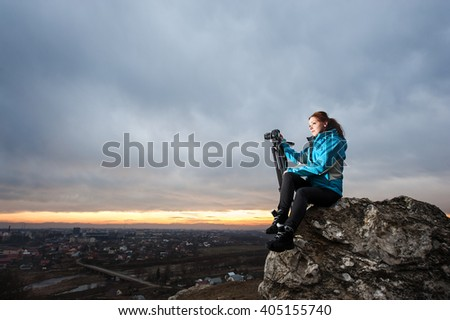 Portrait of cute female photographer sitting on the big rock at city overview point at the sunset with her camera on tripod. Woman is enjoying of the beautiful view - stock photo