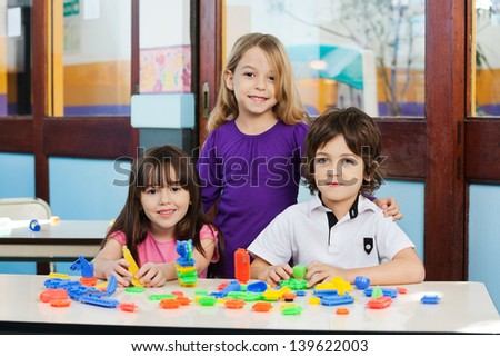 Portrait of cute friends with construction blocks on desk in classroom