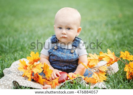 Portrait of cute funny adorable blond Caucasian baby boy with blue eyes in tshirt and jeans romper sitting on grass field meadow, yellow autumn fall leaves. Halloween, Thanksgiving.