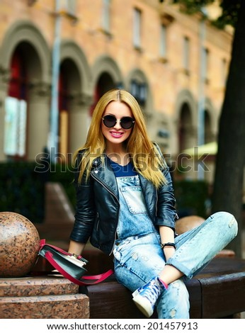 portrait of cute funny blond modern sexy urban young stylish smiling woman girl model in bright modern cloth outdoors sitting in the park in jeans on a bench in glasses