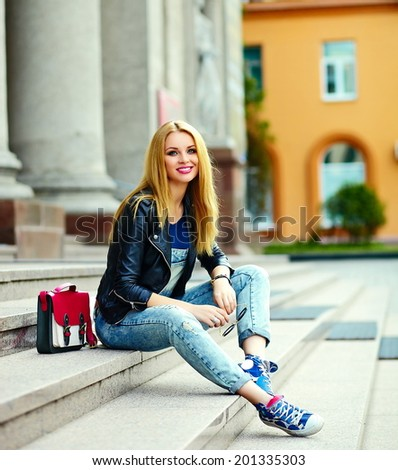 portrait of cute funny modern sexy urban young stylish smiling woman girl model in bright modern cloth outdoors sitting in the city  in jeans with pink bag
