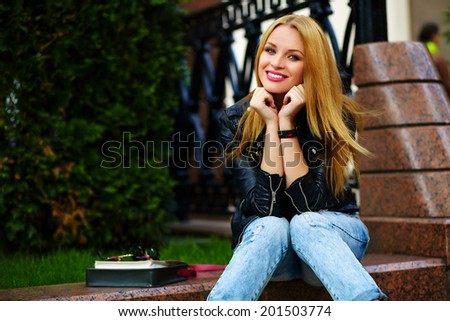 portrait of cute funny modern sexy urban young stylish smiling woman girl model in bright modern cloth outdoors sitting in the park in jeans on a bench
