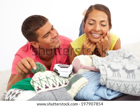 Portrait of cute girl and handsome guy lying on suitcase full of winter clothes - stock photo