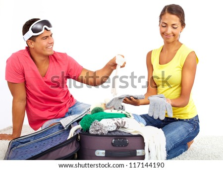 Portrait of cute girl and handsome man choosing clothes for winter resort - stock photo