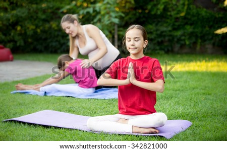 Portrait of cute girl doing yoga during outdoor lesson at park - stock photo
