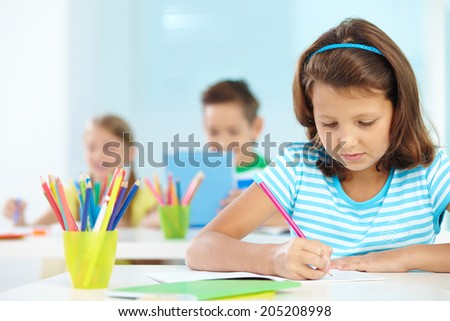 Portrait of cute girl drawing at workplace with her schoolmates on background - stock photo