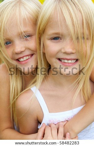 Portrait of cute girl embracing her twin sister and both looking at camera with smiles - stock photo