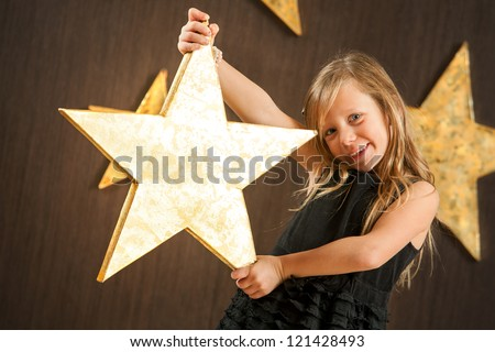 Portrait of cute girl holding big golden star.