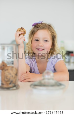 Portrait of cute girl holding cookie at counter in kitchen - stock photo
