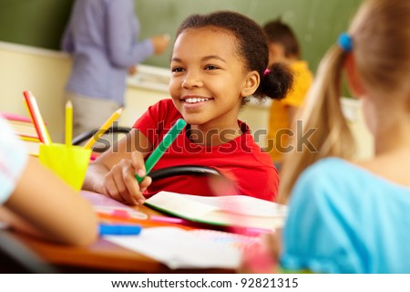Portrait of cute girl holding crayon while looking at classmate at lesson - stock photo