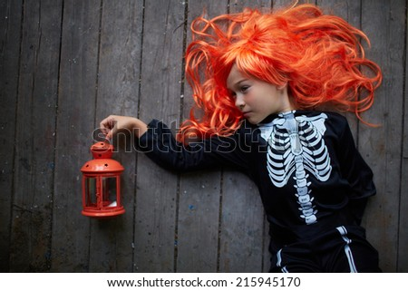 Portrait of cute girl in red wig and Halloween costume - stock photo