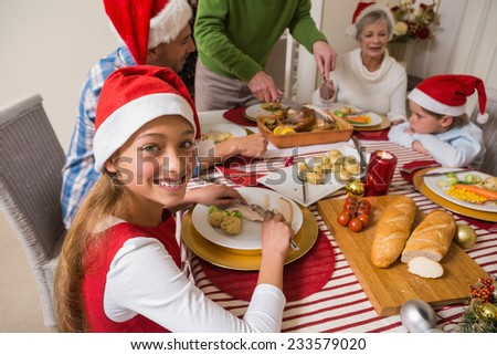 Portrait of cute girl in santa hat during christmas dinner at home in the living room - stock photo