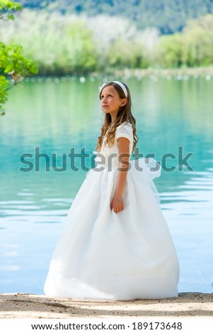 Portrait of cute girl in white dress standing at riverside. - stock photo