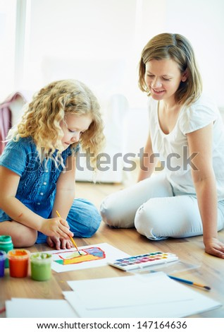 Portrait of cute girl painting with colorful gouache with her mother near by