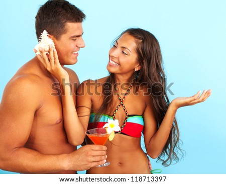 Portrait of cute girl placing seashell against the ear of handsome man with cocktail