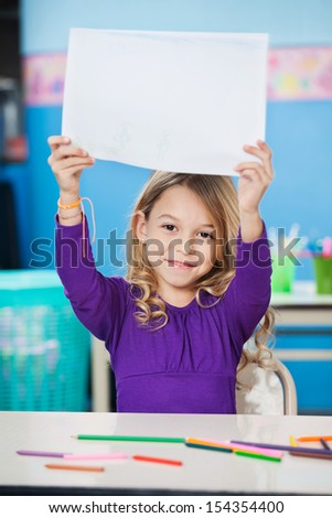 Portrait of cute girl showing blank paper at classroom desk - stock photo