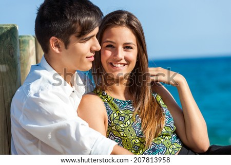 Portrait of Cute girl sitting next to boyfriend at sea side. - stock photo