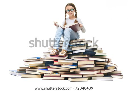 Portrait of cute girl sitting on pile of books and looking at camera - stock photo