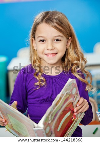 Portrait of cute girl smiling while holding book in kindergarten - stock photo