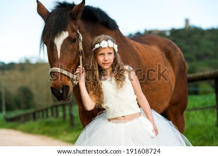 Portrait of cute girl wearing flower crown standing next to horse outdoors. - stock photo