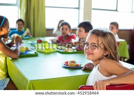 Portrait of cute girl with classmates having meal in canteen