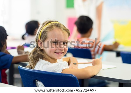 Portrait of cute girl with classmates in classroom