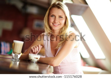 Portrait of cute girl with dessert sitting in cafe - stock photo