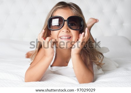 Portrait of cute girl with eyewear lying barefoot in the bed