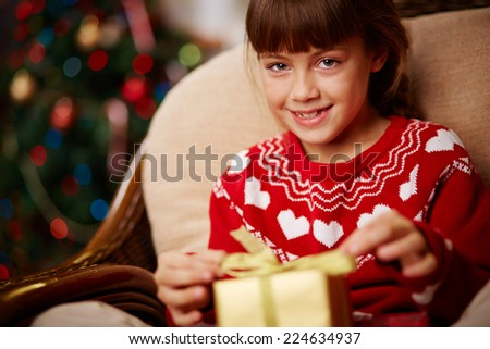 Portrait of cute girl with giftbox looking at camera