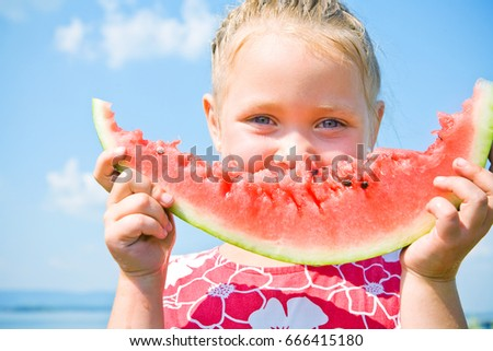Portrait of cute girl with peace of red watermelon on blue sky background