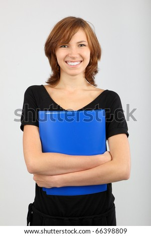 Portrait of cute girl with textbook in hands grey background - stock photo