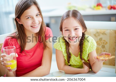 Portrait of cute girls sitting by dinner table and looking at camera - stock photo