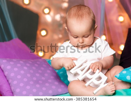 Portrait of cute happy baby sitting against the backdrop of garlands - stock photo