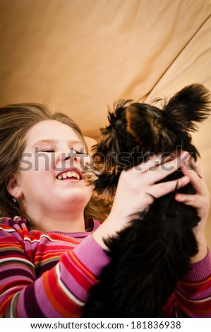 Portrait of cute happy child (girl) playing with little dog - stock photo