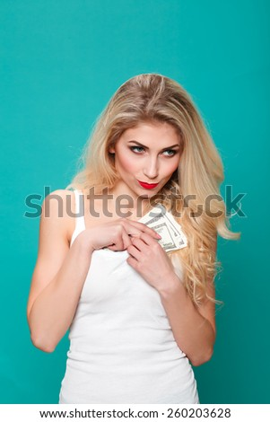Portrait of cute happy girl holding in hand a lot american dollars, hides money in blouse,  hides dollars. - stock photo
