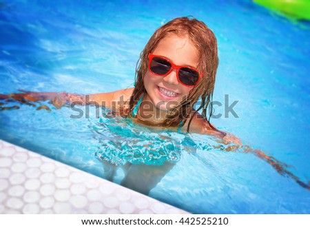 Portrait of cute happy little girl having fun in swimming pool, adorable baby spending summer vacation on the beach resort  - stock photo