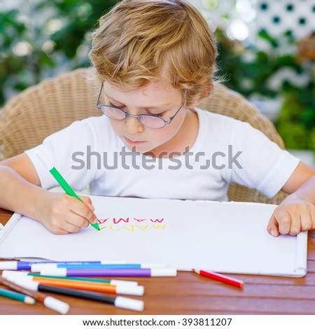Portrait of cute happy preschool kid boy with glasses at home making homework. Little child painting with colorful pencils, indoors. School, education concept