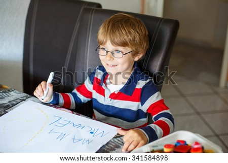 Portrait of cute happy preschool kid boy with glasses at home making homework. Little child writing mama with colorful pencils, indoors. School, education concept - stock photo