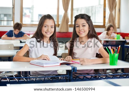 Portrait of cute happy schoolgirls sitting with book at desk while friends studying in background - stock photo