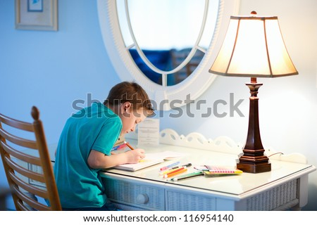 Portrait of cute happy schoolkid at home drawing or writing - stock photo