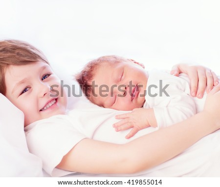 portrait of cute happy siblings. young boy holding his infant brother - stock photo