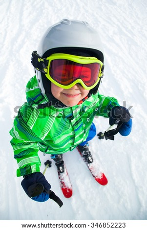Portrait of Cute happy skier boy in a winter ski resort.