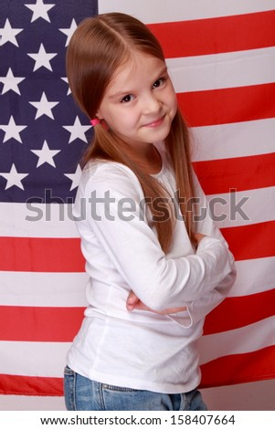 Portrait of cute happy smiling little girl on the background of a large American flag/American Independence Day