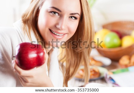 Portrait of cute happy woman eating red ripe apple for breakfast, fruit diet, organic nutrition, healthy lifestyle