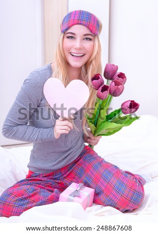 Portrait of cute happy woman sitting on the bed and enjoying gifts, receive tulip bouquet, romantic relationship, Valentine day concept - stock photo
