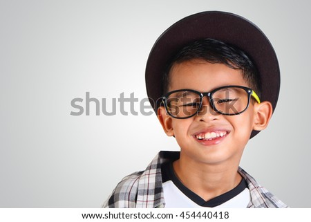 Portrait of cute happy young Asian boy wearing hat and glasses smiling - stock photo