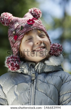 Portrait of cute happy young girl in warm clothes smiling at yard