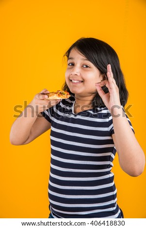 portrait of cute indian girl eating pizza over yellow background - stock photo